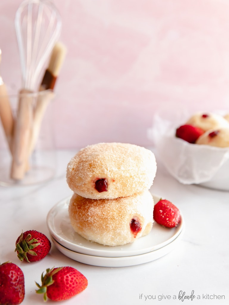 two jelly filled donuts stack o top of each other with fresh strawberries next to them