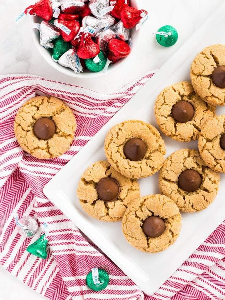 peanut butter blossoms on white rectangle plate with red striped kitchen cloth underneath plate