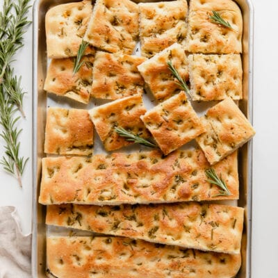 focaccia bread on large baking pan; half the bread cut into squares; rosemary next to pan