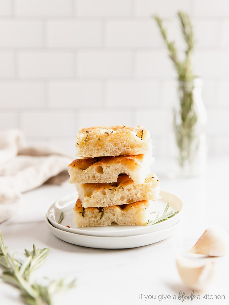 stack of four focaccia bread squares stack on top of each other on small white plate