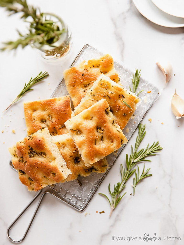 focaccia squares on small wire cooling rack. rosemary sprigs and garlic cloves next to rack
