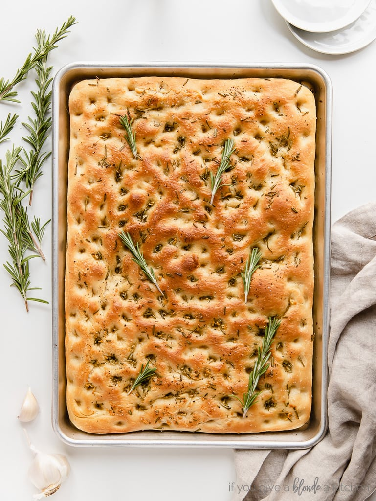 uncut focaccia bread on baking pan with fresh rosemary sprigs