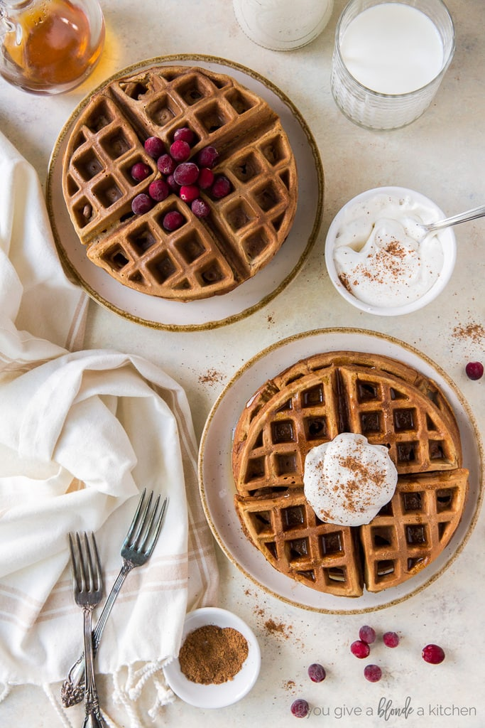 two plates of gingerbread waffles; one stack with cranberries; one stack with eggnog whipped cream