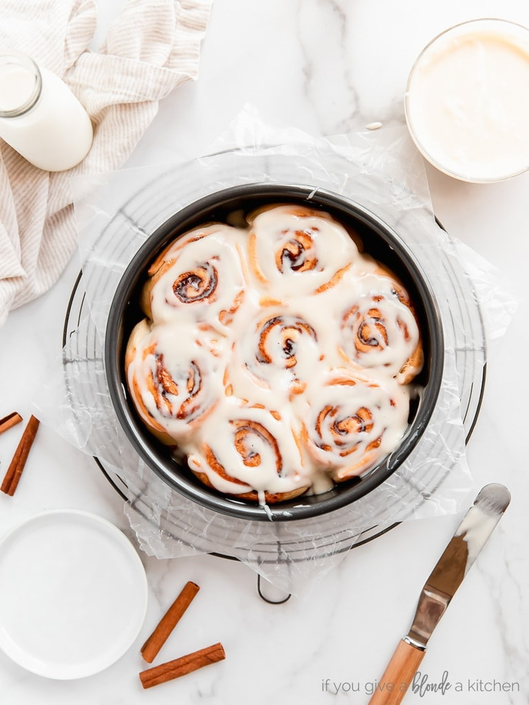 cinnamon rolls with cream cheese icing in round cake pan on round wire rack