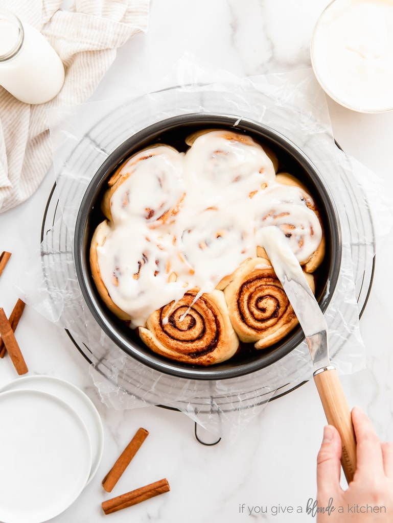 hand holding offset spatula spreading cream cheese icing over cinnamon rolls in round pan