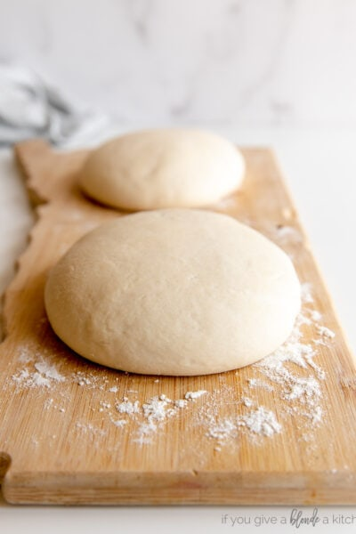 two pizza dough balls on floured wooden board
