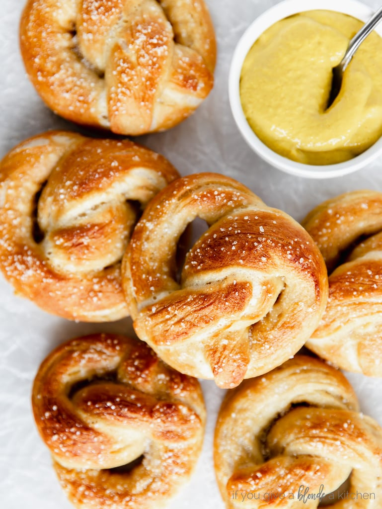 soft pretzels face up on top of each other; white bowl of mustard with spoon next to pretzels