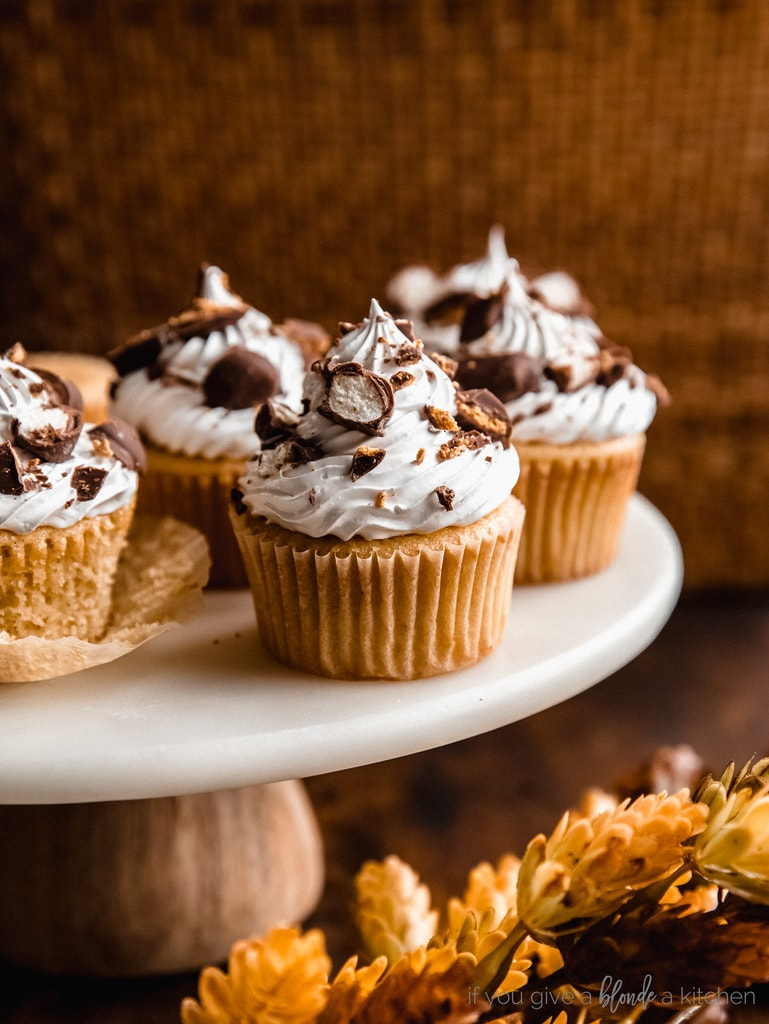 maple cupcakes with marshmallow frosting on marble cake stand on dark brown tabletop with leaves