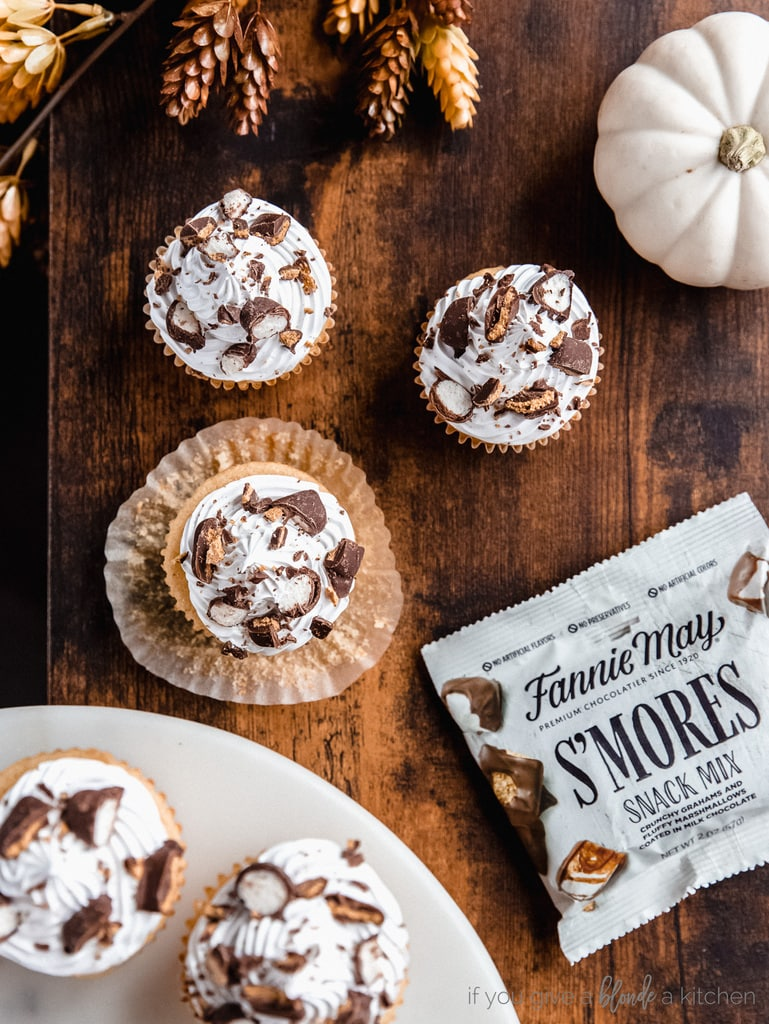 cupcakes with white frosting and candy bits on top; dark wood background with leaves and white pumpkin