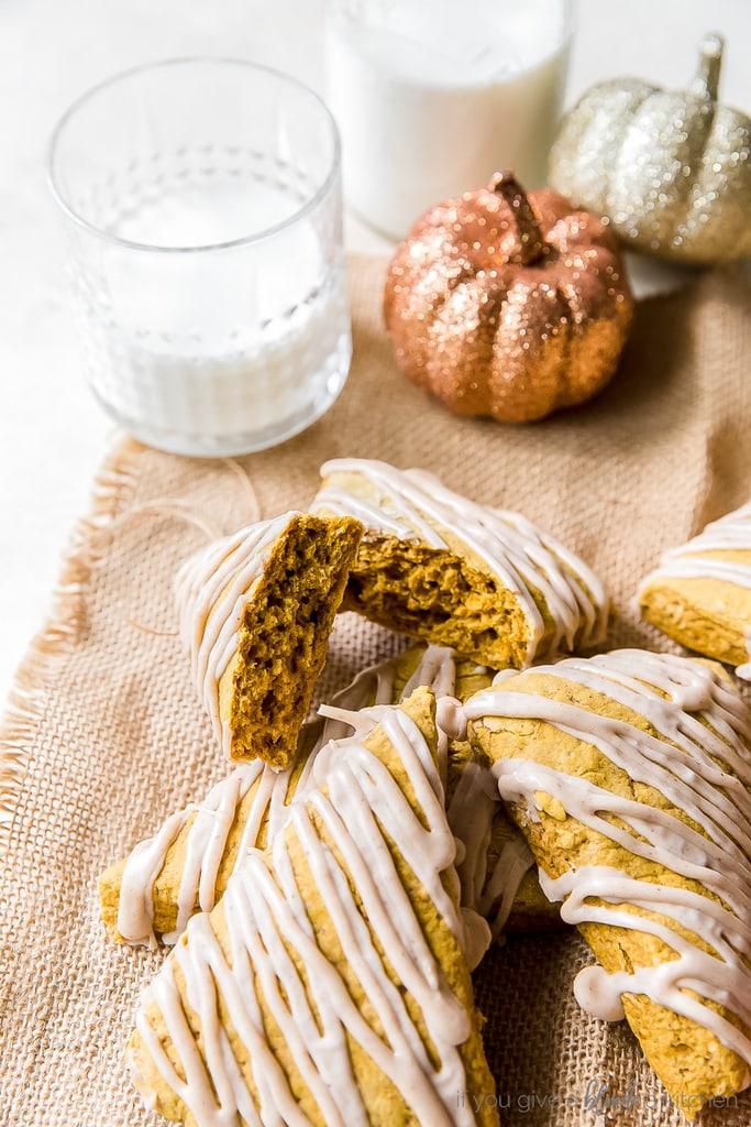pumpkin scone broken in half to show inside; more scones with drizzle on burlap