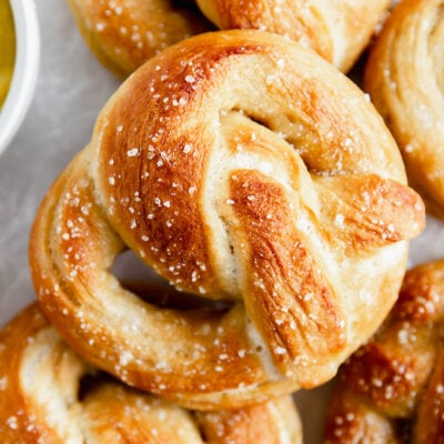 homemade soft pretzel with salt on top of more soft pretzels