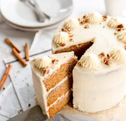 cake server taking slice of three layer carrot cake out of round cake