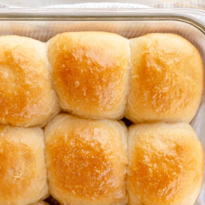 golden dinner rolls side by side in a glass baking pan