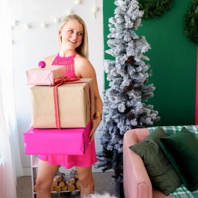 blonde girl in bright pink dress holding stack of christmas presents