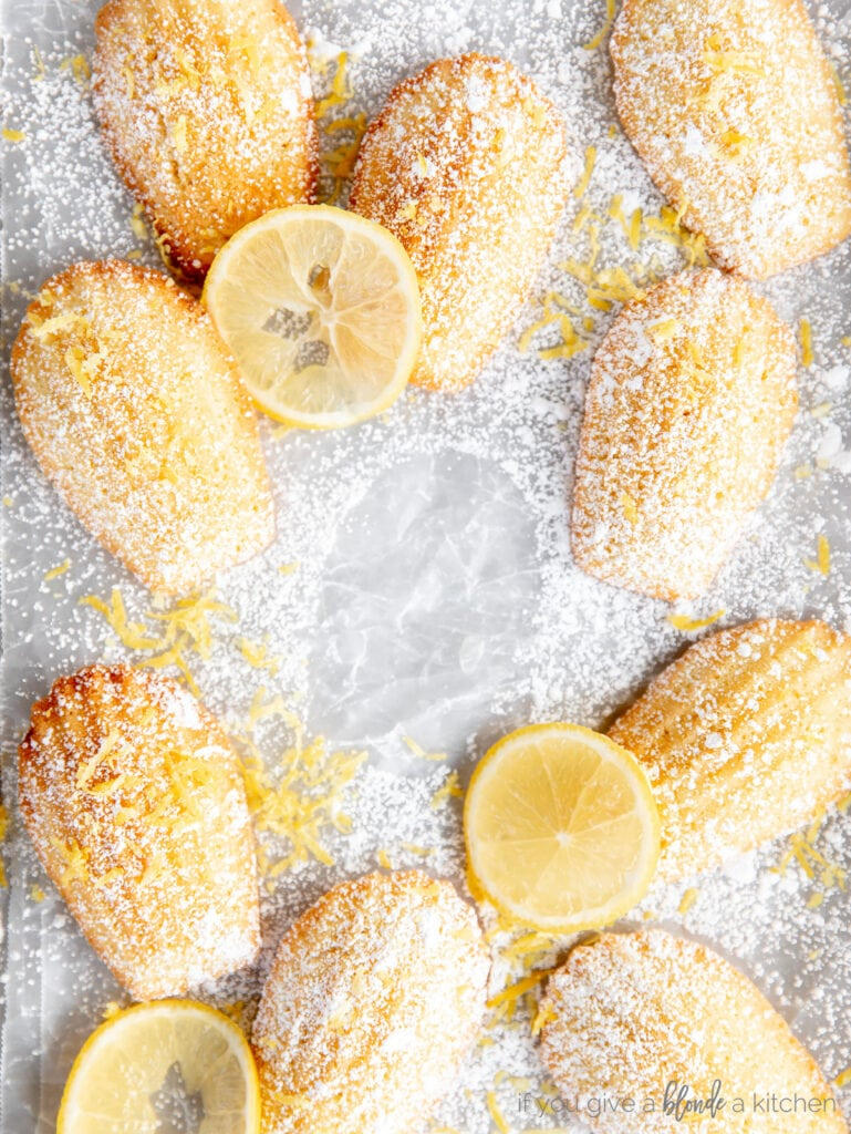 madeleines on parchment paper with lemon slices and dusting of confectioners' sugar