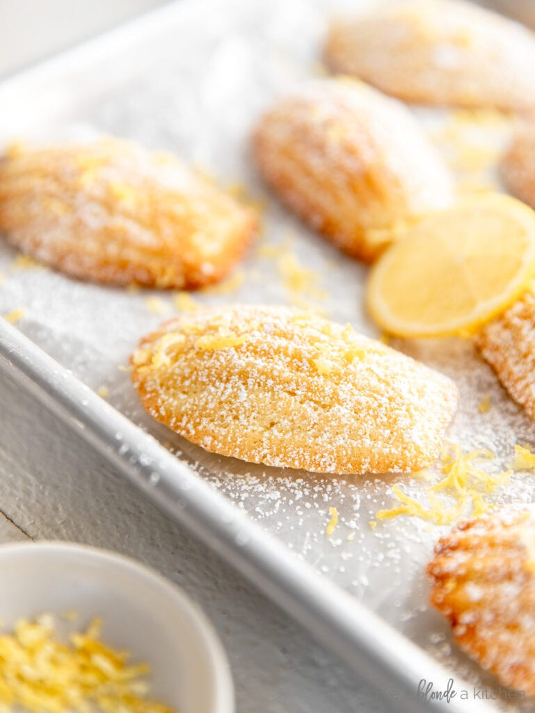madeleine cookies on baking sheet with dusting of confectioners' sugar and lemon zest