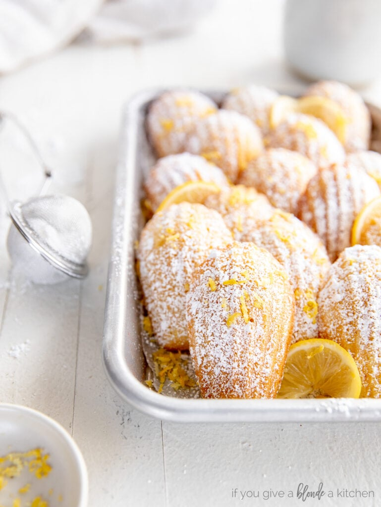 madeleine cookie leaned up against more madeleines layered in baking sheet.