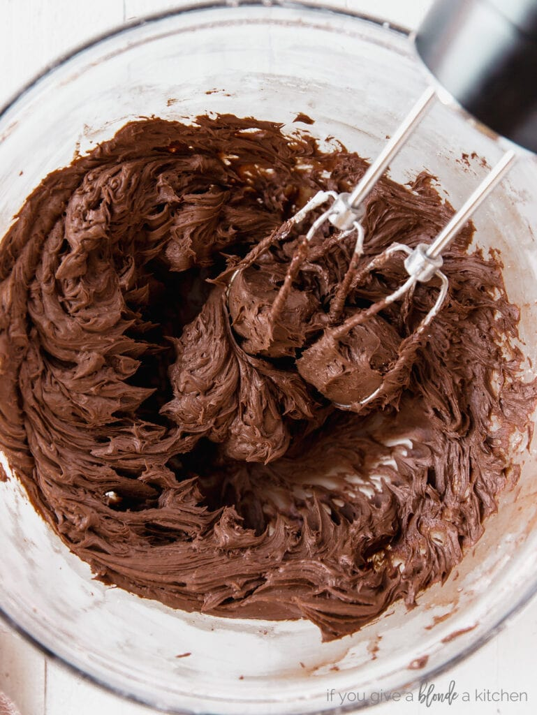 bowl of chocolate frosting with beaters of hand mixer in the frosting