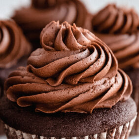 chocolate buttercream frosting on top of cupcakes