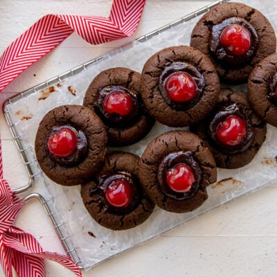 hand reaching for chocolate cherry thumbprint cookie on wire cooling rack with handle tied with ribbon