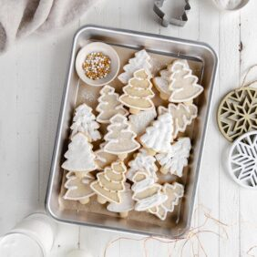 iced cut out christmas tree sugar cookies on rectangle baking sheet