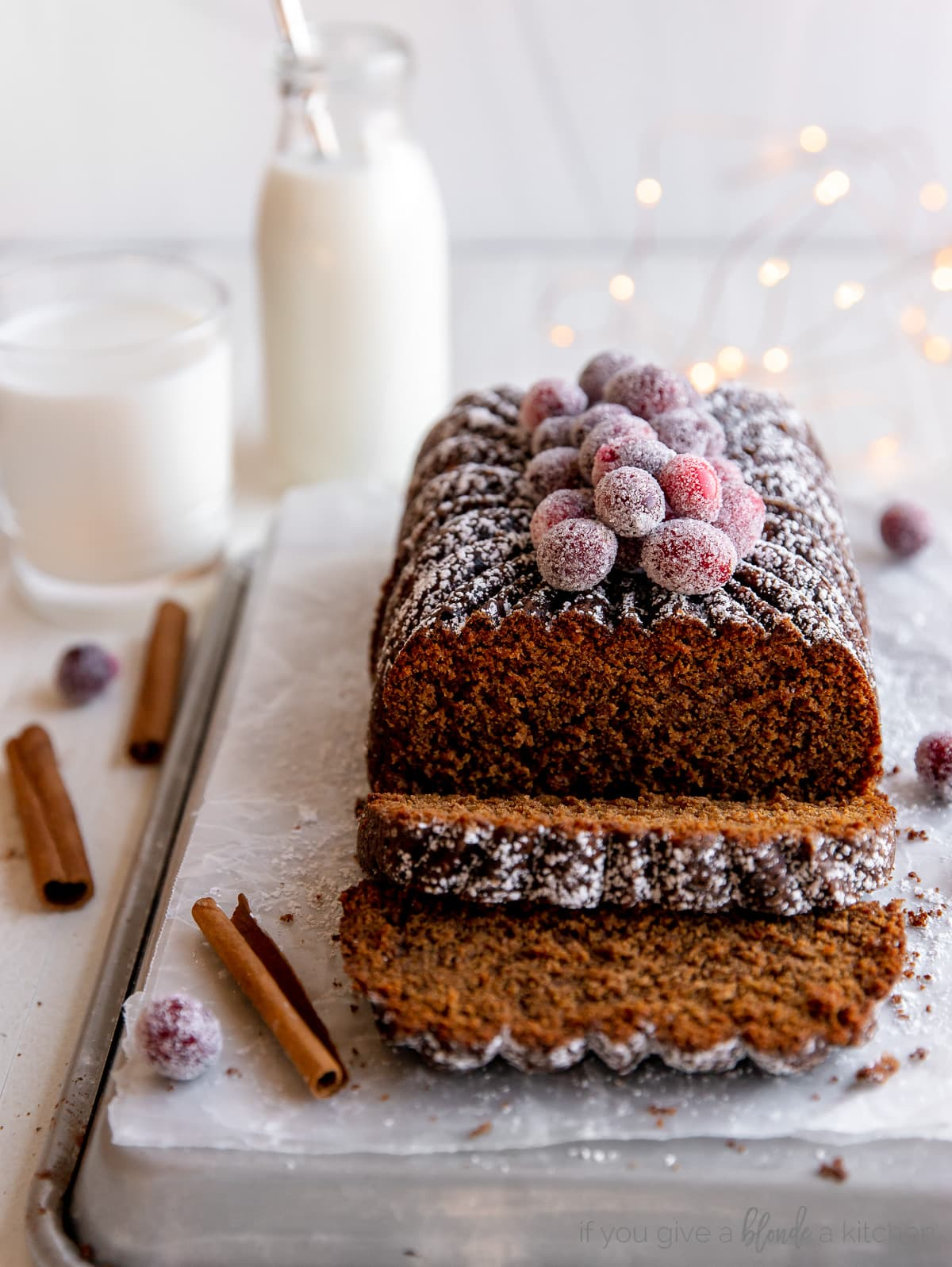 gingerbread loaf with two slices cut off the end; loaf topped with sugared cranberries and confectioners' sugar