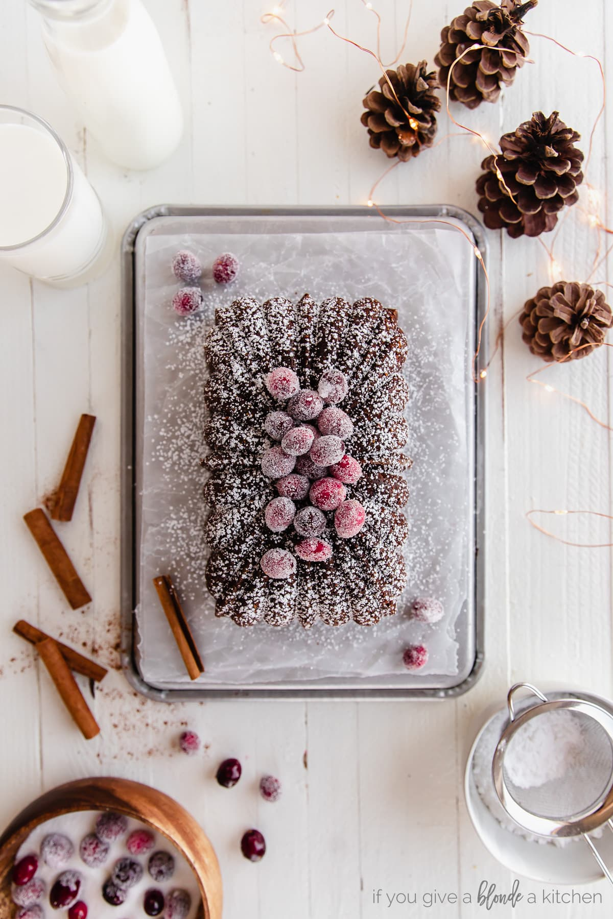 gingerbread loaf dusted with confectioners sugar and topped with sugared cranberries on baking sheet