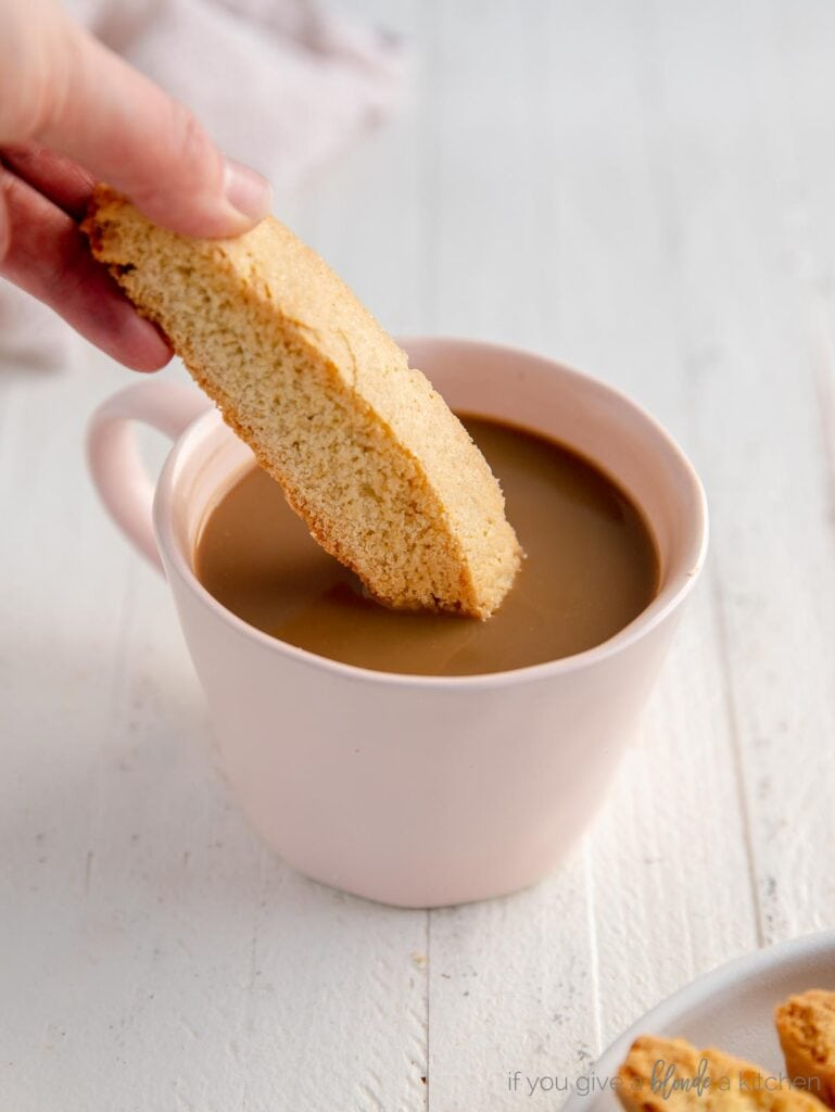 hand dipping biscotti in pink mug of coffee