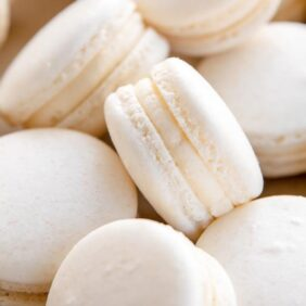 white macaron with buttercream filling leaning on its side on top of other macarons