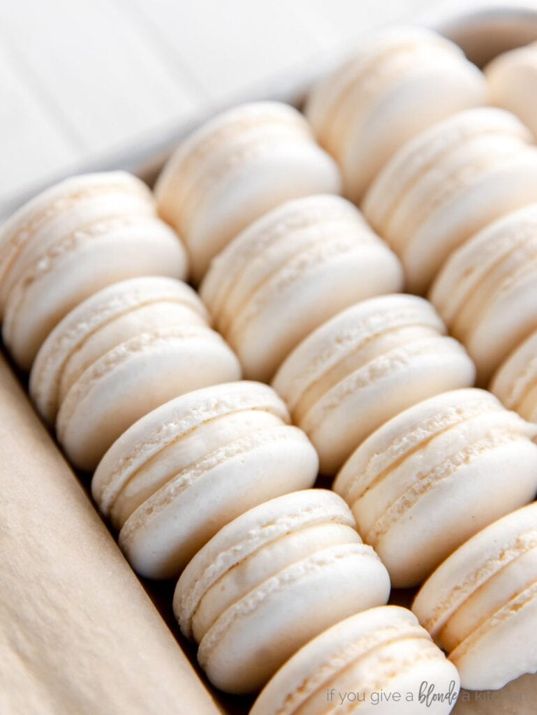 macarons with buttercream filling lined up in rows on a baking sheet