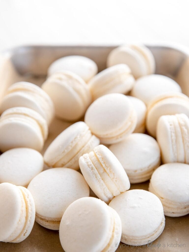 simple white macarons piled on a small baking sheet