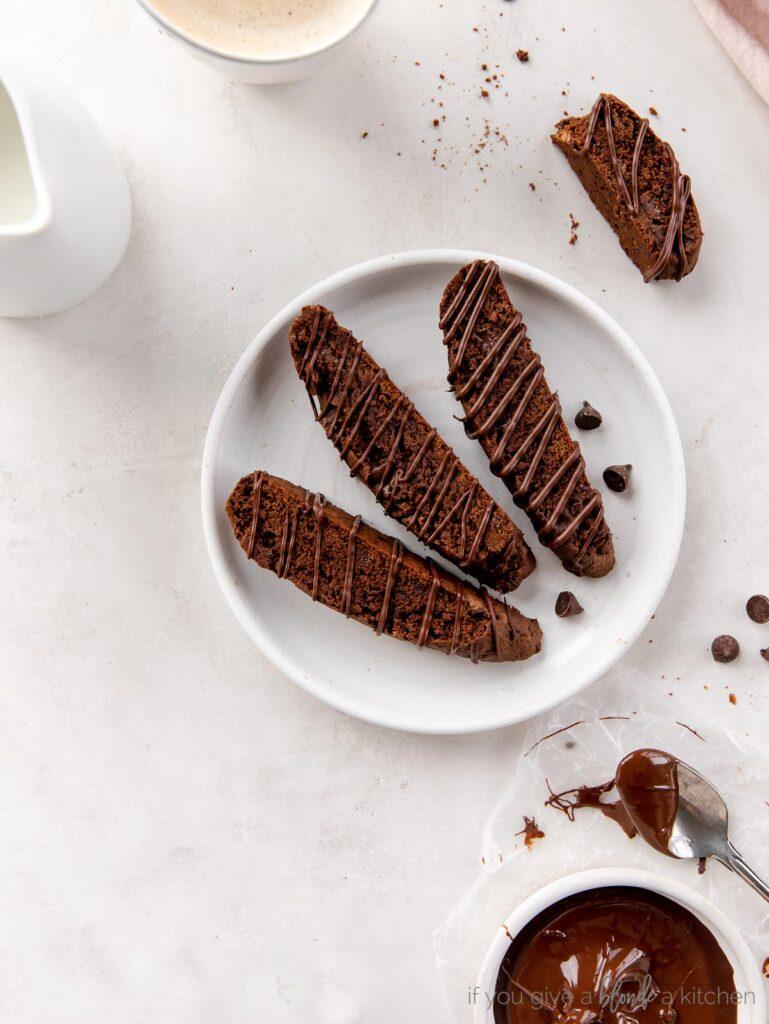 three chocolate biscotti on round white plate, half eaten biscotti next to plate with crumbs