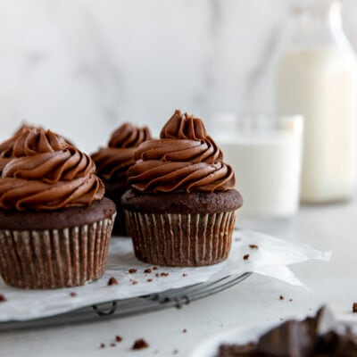 chocolate cupcake with chocolate frosting on wire rack with glass bottle of milk behind cupcakes