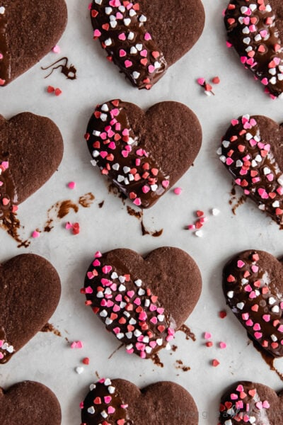 chocolate cut out cookies in a heart shape dipped in chocolate with red and pink sprinkles on tpo