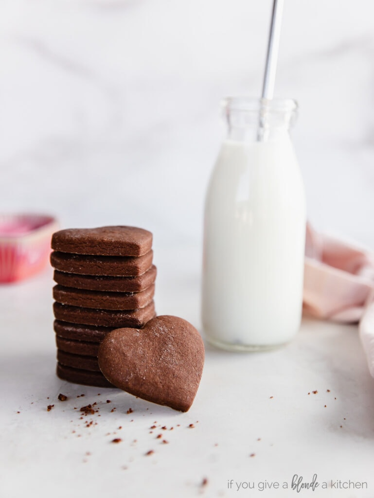 stack of chocolate cut out cookies next to glass jar of milk