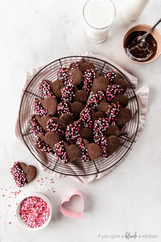 chocolate heart cookies with melted chocolate and red and pink sprinkles on round wire cooling rack