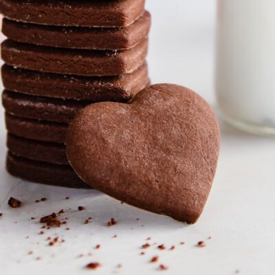 heart shaped chocolate cut out cookie leaning up against stack of cookies
