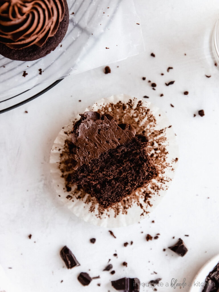 chocolate cupcake with chocolate frosting cut in half on top of paper liner