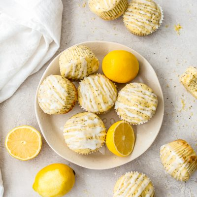lemon poppy seed muffins and lemon wedges on a plate and table surface