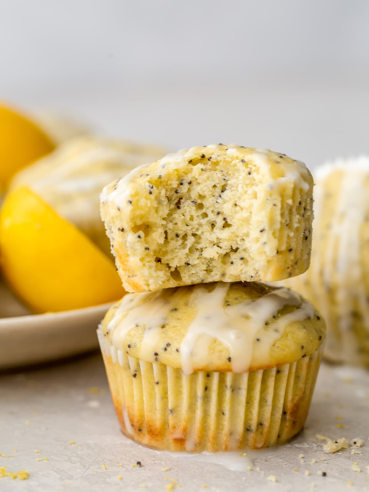 lemon poppy seed muffin with a bite stacked on top of another muffin
