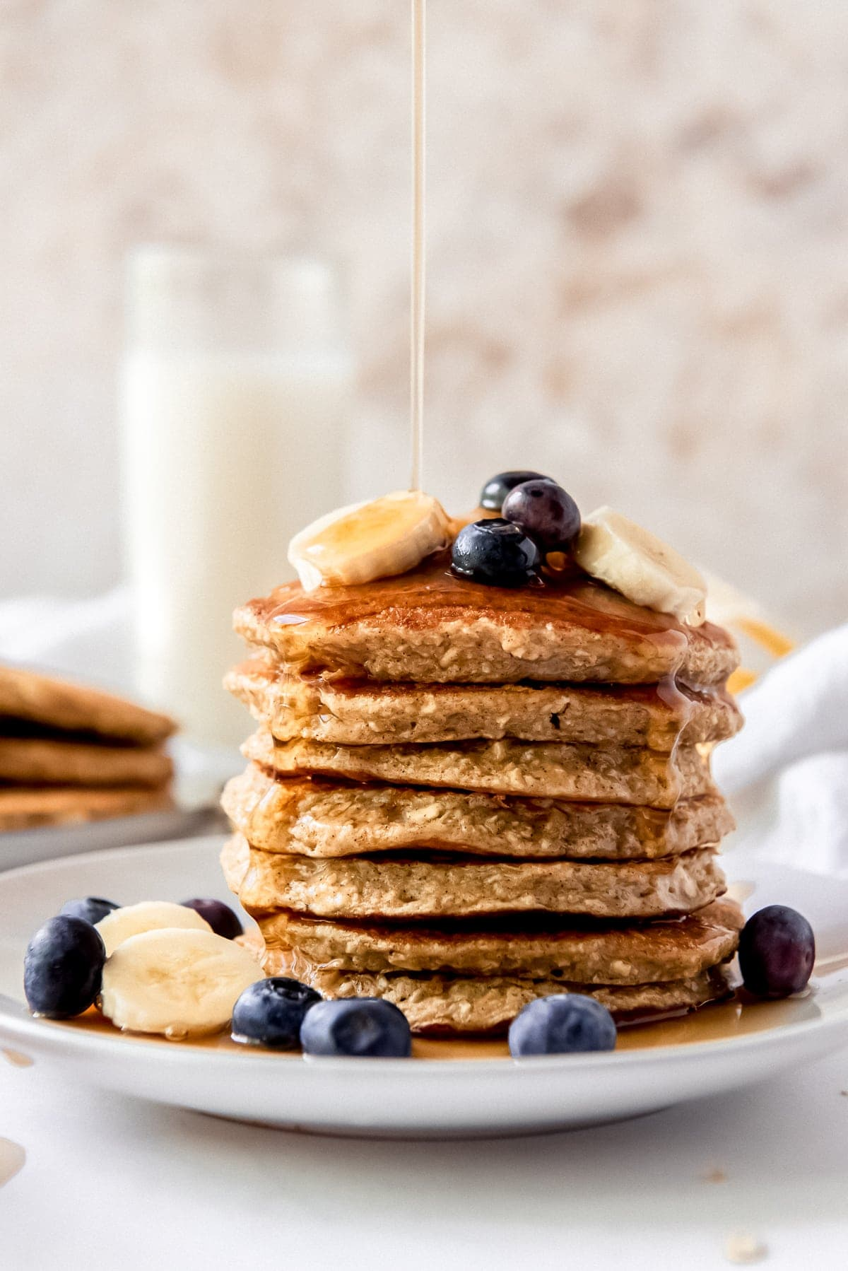 maple syrup poured on a stack of banana oatmeal pancakes with sliced bananas and blueberries