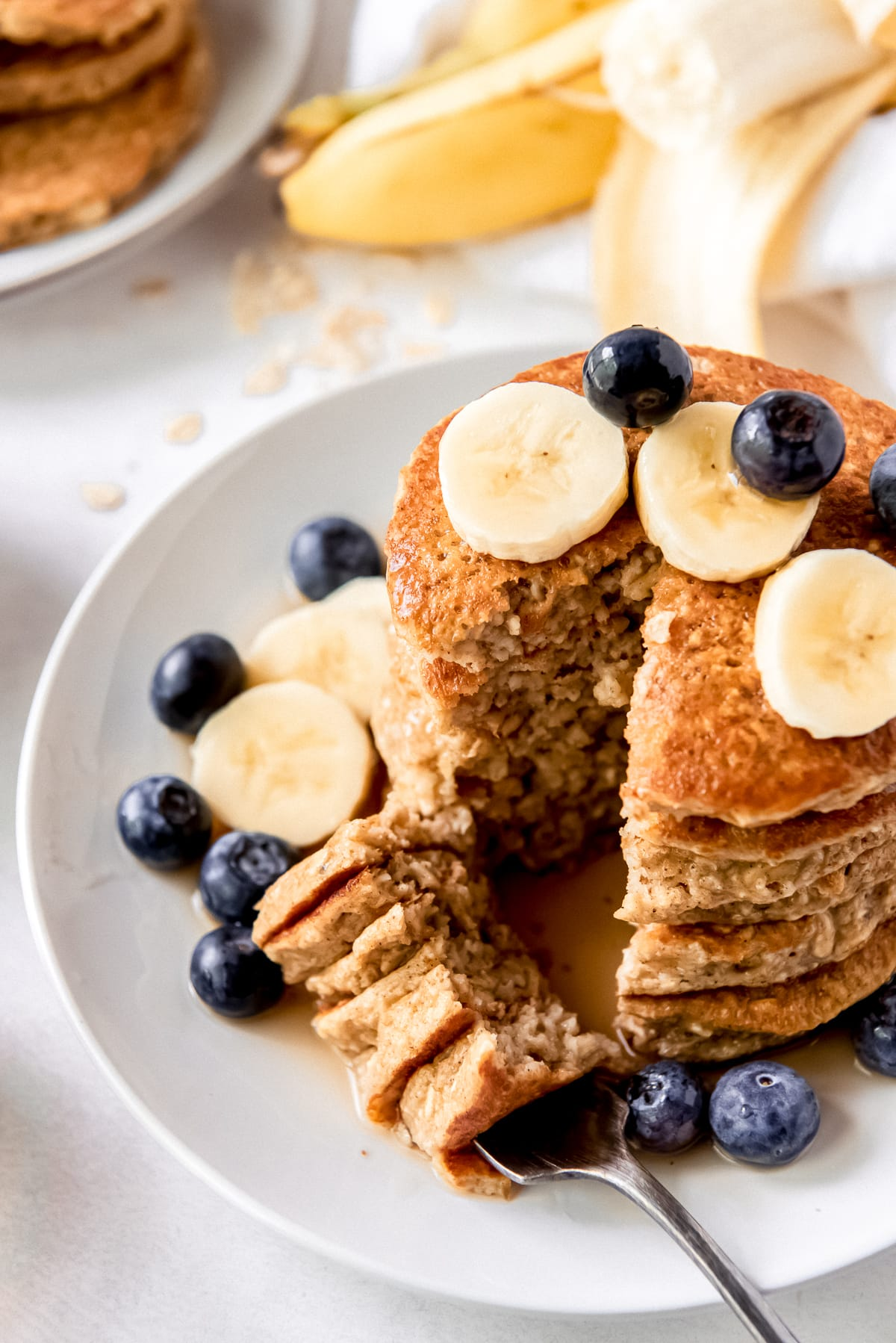 stack of banana oatmeal pancakes on plate with fork holding a bite