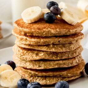 stack of banana oatmeal pancakes on white plate with banana slices and blueberries