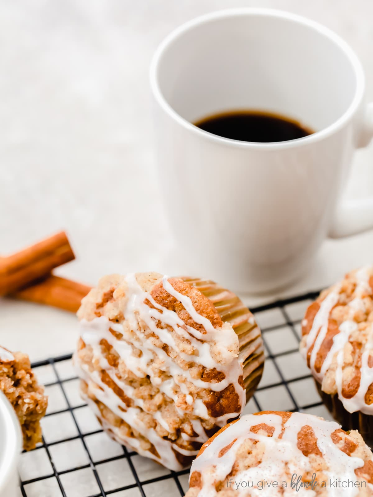 coffee cake muffin with icing turned on its side next to white mug of coffee