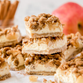 stack of three apple cheesecake bars in front of more bars and apples