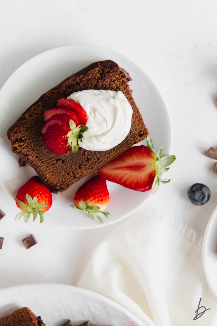 slice of chocolate pound cake on plate with whipped cream and strawberries