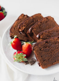 slices of chocolate pound cake on white plate with strawberries