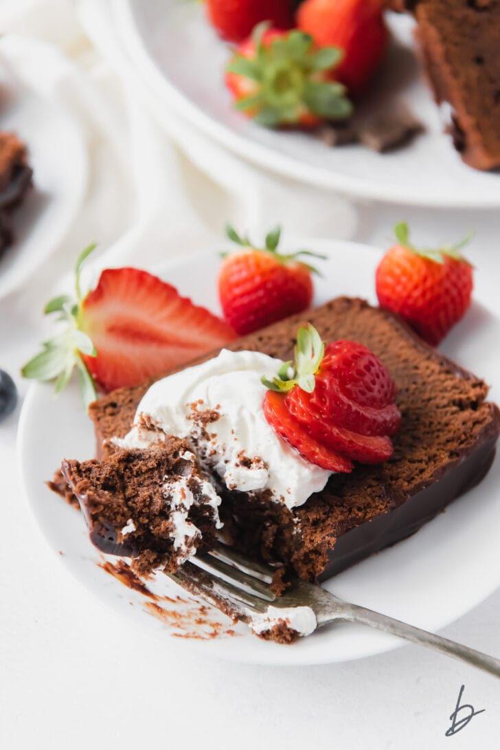 fork taking bite our of a slice of chocolate pound cake with whipped cream and strawberries