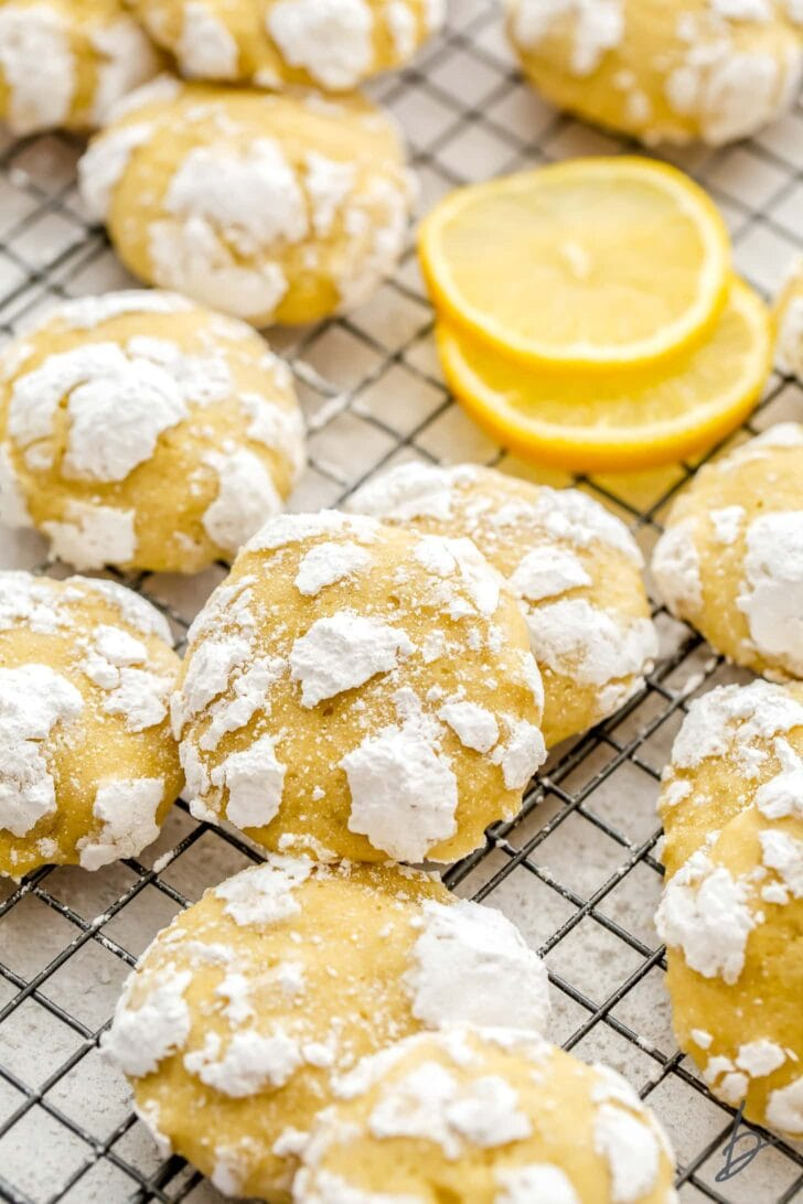 lemon crinkle cookies with confectioners sugar piled on wire rack