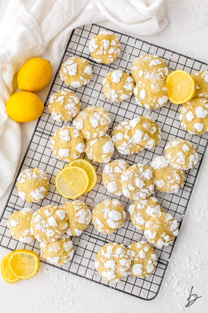 lemon crinkle cookies on wire cooling rack with lemons